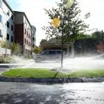 Sprinklers watering grass in parking lot