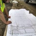 man looking at irrigation system blueprints